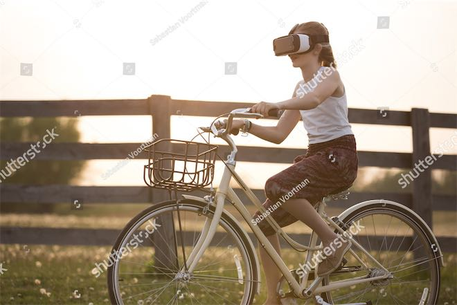 Woman riding bicycle while wearing VR headset